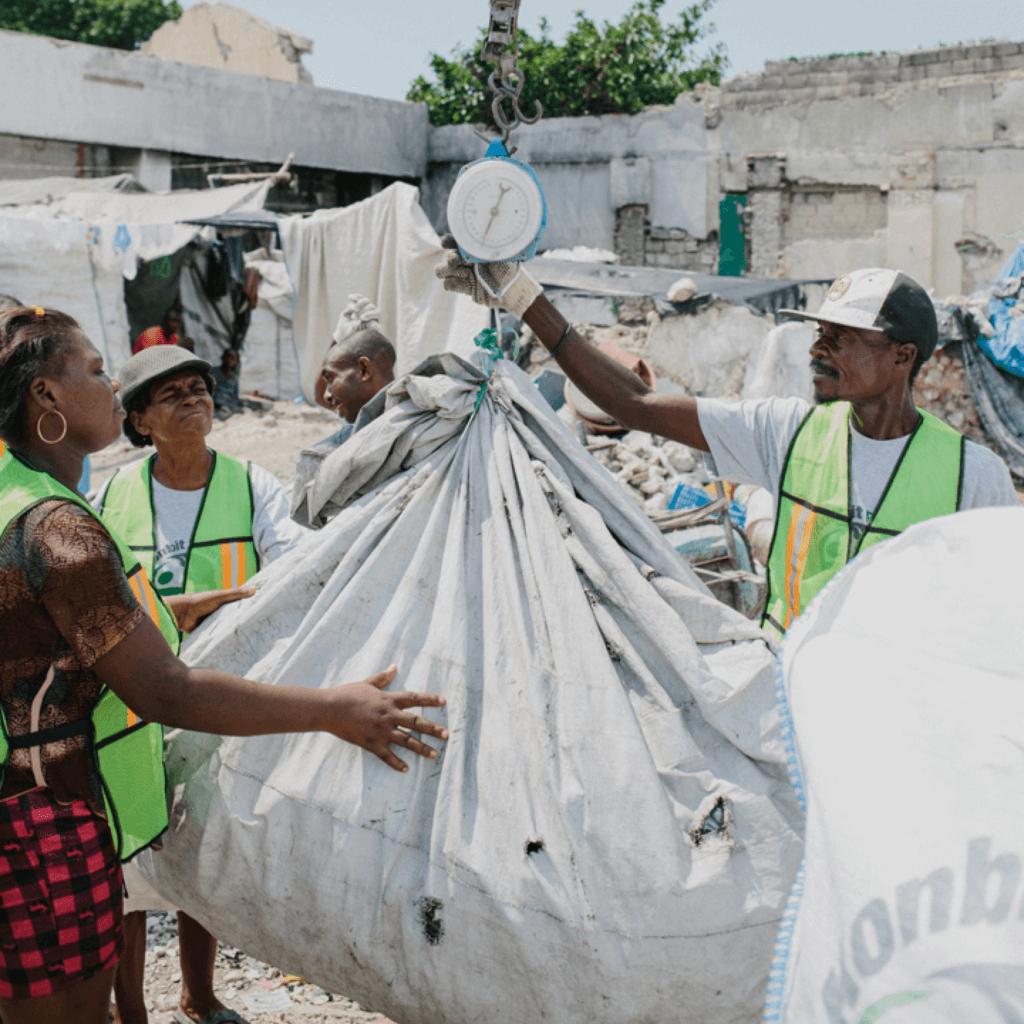 Haitianische Arbeiter auf Recyclinghof, wiegen in großen Plastiksäcken diePlastikflachen