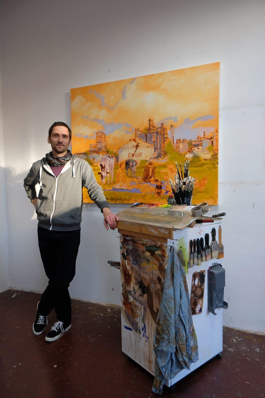 Maler in seinem Atelier vor einem seiner Werke, lehnt sich an den Rollwagen mit Farben und Pinseln