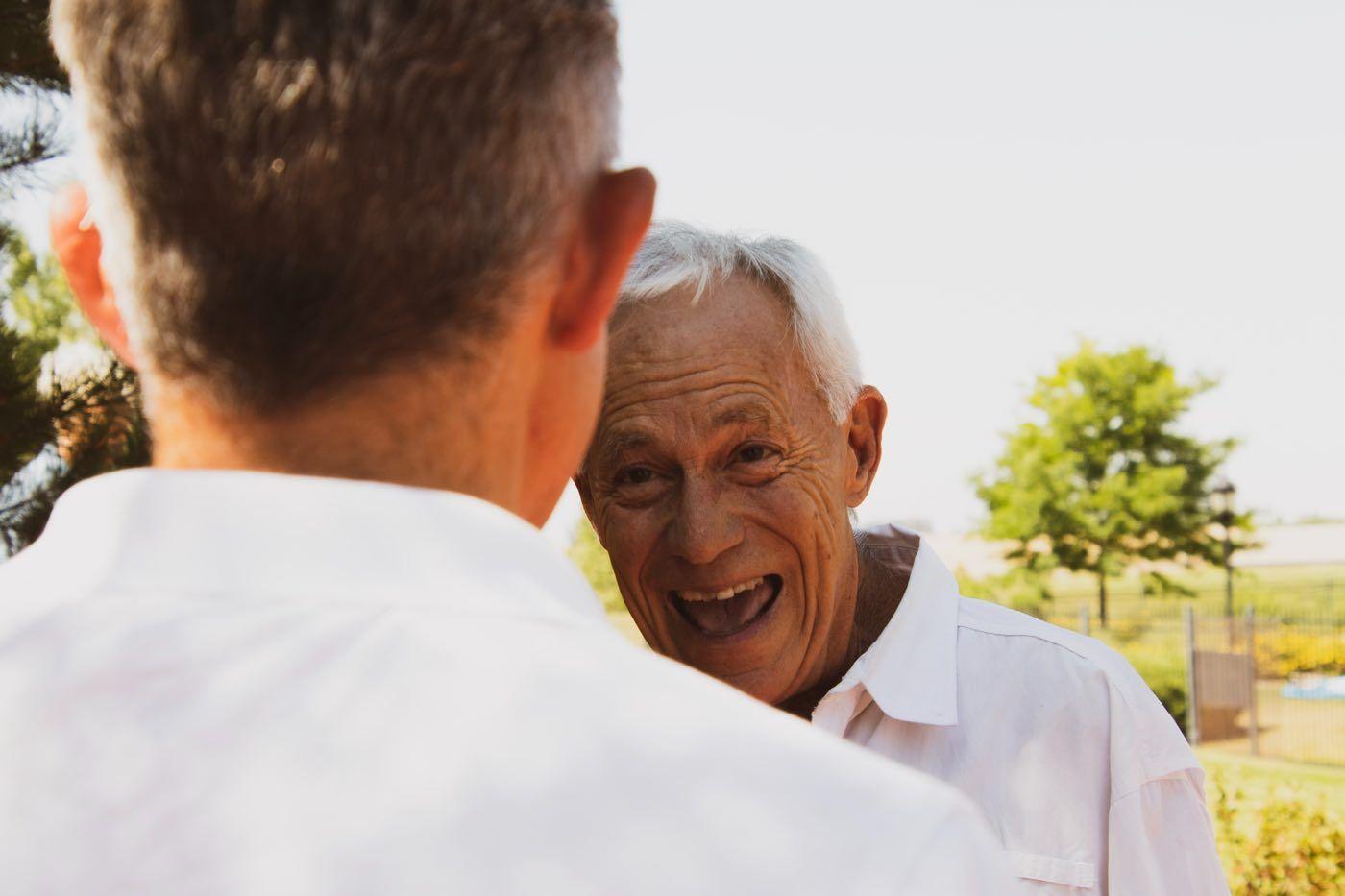 Zwei alte Männer, der eine lacht breit Richtung Kamera, der andere nur von hinten zu sehen