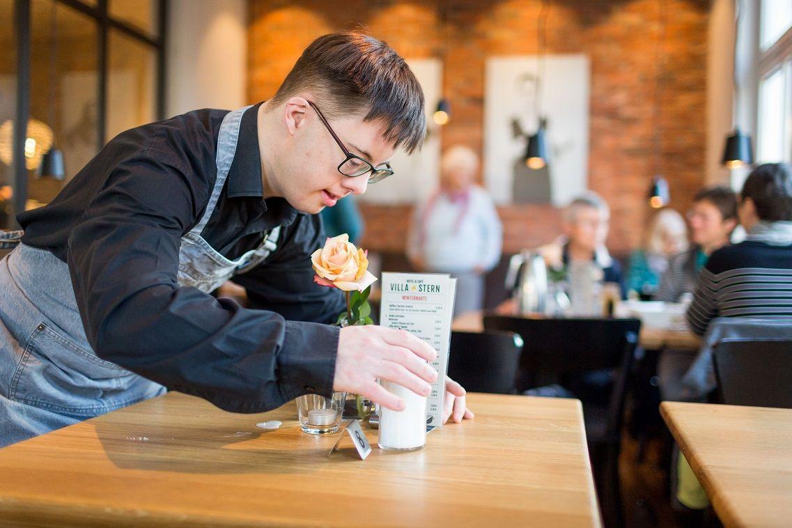 Junger Mann mit Downsyndrom deckt in Restaurant einen Tisch ein (nachhaltige Unternehmen beschäftigen Menschen mit Behinderung)