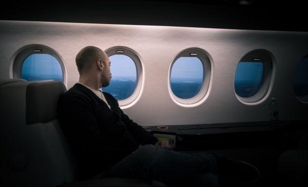 Passagier in der First Class eines Flugzeuges, schaut aus dem Fenster