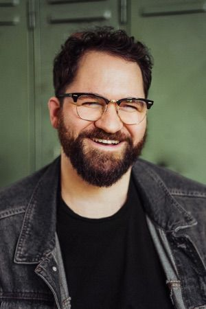 Mann mit Vollbart und Retrobrille, dunkelblondes Haar, schwarzes T-Shirt, Jeansjacke, er lacht