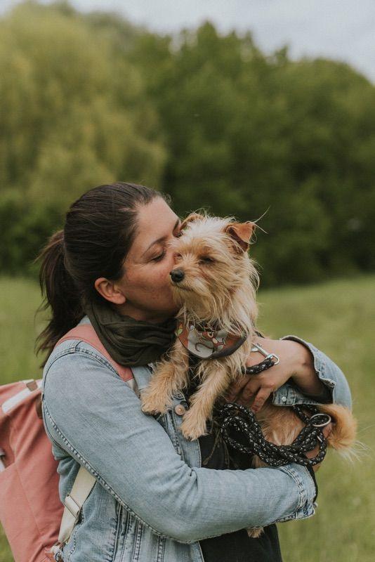 Junge Frau hält kleinen Hund auf dem Arm und drückt ihr Gesicht in sein Fell