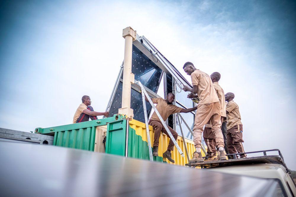 Afrikanische Handwerker errichten einen Solarkollektor auf einem Dach