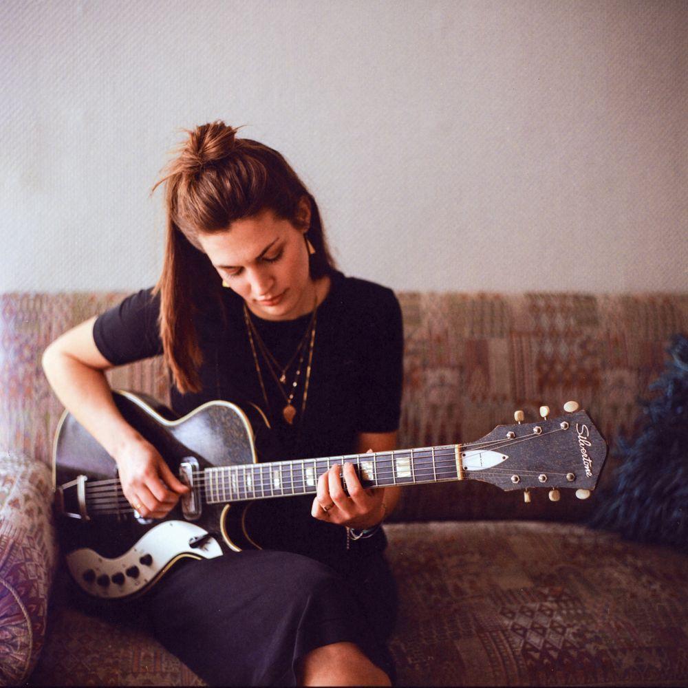 Frau mit langen braunen Haaren und schwarzem Kleid sitzt auf Sofa und spielt Gitarre