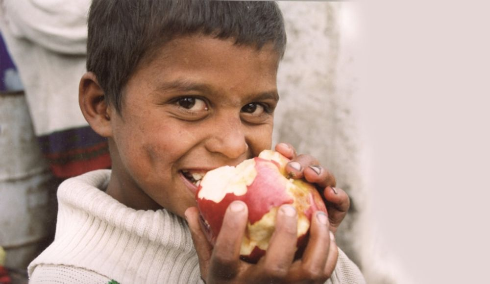 Little Roma boy takes a hearty bite of a big red apple