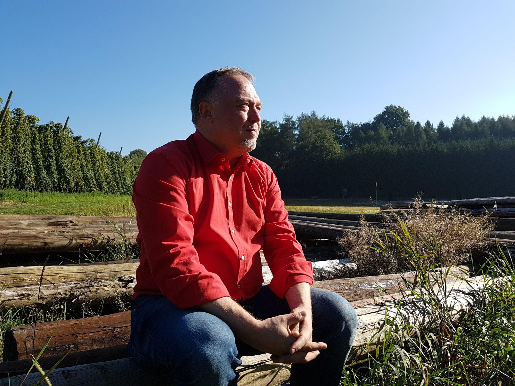 Mann Mitte 50, rotes Hemd und Jeans, sitz auf einem Baumstamm in schöner Naturlandschaft unter blauem Himmel