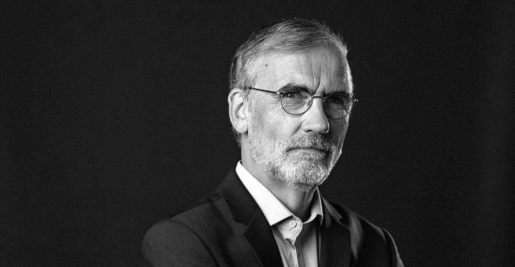 Schwarz-weiß-Foto zeigt einen älteren Herrn in Anzug mit grauen Haaren, Bart und Brille, er blickt ernst in die Kamera