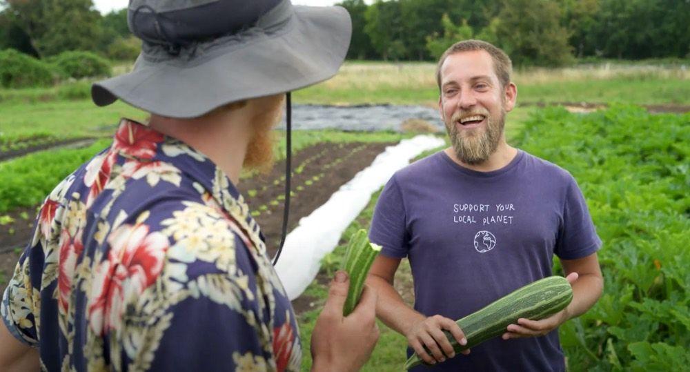 Junger Bauer mit blondem Kurzhaar und Vollbart hält eine große Zucchini in der Hand und lacht